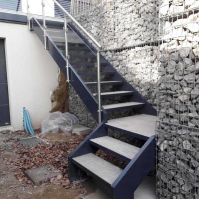 Escalier extérieur en métal et pierre tournant sur la partie basse